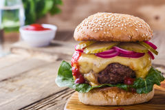 Burger with  gherkins, red onion and lettuce. On wooden table, rustic style Royalty Free Stock Images