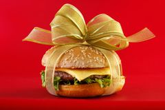 Burger for gift. Gift wrapped hamburger , conceptual food image with red background Stock Photography