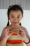 Burger girl. Chinese girl smiling and holding a hamburger Stock Image
