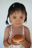Burger girl. A little girl smiling and holding a hamburger Stock Image