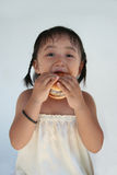 Burger Girl. A little girl holding and biting a hamburger Royalty Free Stock Photography