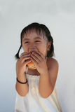 Burger girl. A little girl laughing and biting a hamburger Stock Photo