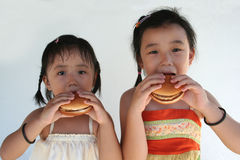 Burger girls. Two little girls holding and biting a hamburger Royalty Free Stock Image