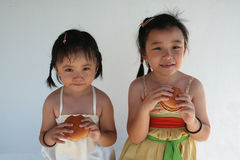 Burger girls. Two little girls holding and biting a hamburger Stock Photography