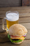 Burger with glass of beer on wooden table Stock Images