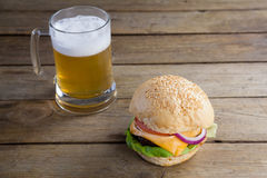 Burger with glass of beer on wooden table Royalty Free Stock Images