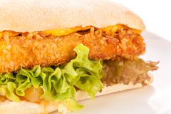 Burger with golden crumbed chicken breast. Closeup of a tasty burger with a golden crispy crumbed chicken breast topped with melted cheese and fresh curly stock images