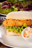 Burger with golden crumbed chicken breast Royalty Free Stock Image