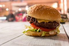 Burger on gray wooden surface. Side view of a hamburger. Feast for stomach Royalty Free Stock Photo
