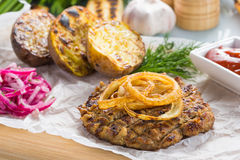 Burger grill with vegetables, sauce on a wooden surface. potatoes and bread Stock Photography