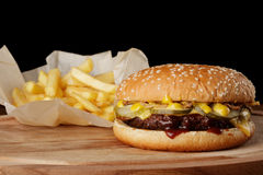 Burger (hamburger) with french fries. And sauce. Wooden background Royalty Free Stock Photo