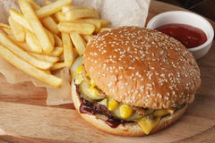 Burger hamburger with french fries. And sauce. Wooden background Stock Images