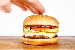 The Burger in the hand of the chef Stock Photography