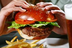 Burger in hands. A delicious juicy burger in hand ready to be eaten Royalty Free Stock Images