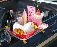 Burger Heaven, lunch at a drive in restaurant. A retro style lunch with hamburger, fries and Sundae ice cream. Tray hanging on the car window at a drivein Stock Photos