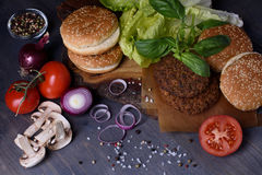 Burger ingredients: beef patties, sesame bun, fresh vegetables, pepper, mushrooms over dark wooden table. Royalty Free Stock Photography