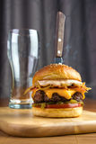 Burger with knife. Homemade gourmet beef burger with empty glass and steak knife Royalty Free Stock Image