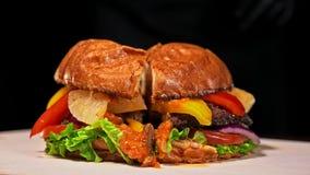 Burger kocht auf schwarzem Hintergrund in den schwarzen Lebensmittelhandschuhen Sehr köstliches Luftbrötchen und gemarmortes Rind stock footage