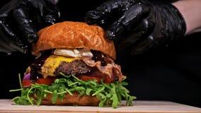 Burger kocht auf schwarzem Hintergrund in den schwarzen Lebensmittelhandschuhen Sehr köstliches Luftbrötchen und gemarmortes Rind stock video footage