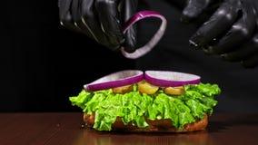 Burger kocht auf schwarzem Hintergrund in den schwarzen Lebensmittelhandschuhen Sehr köstliches Luftbrötchen und gemarmortes Rind stock video