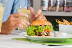 Burger With Man's Hand Holding Drink At Table Stock Photos