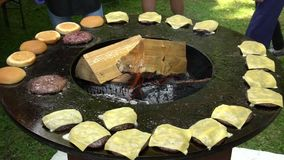 Burger meat, cheese and bread bake on outdoor grill with firewood. Handheld shot. Burger meat, cheese and bread baking on outdoor grill with firewood stock footage