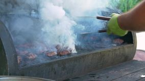Burger meat with flame. Barbecue patty the cook in green gloves grills juicy meat outdoors fire flame smoke slow motion stock video footage