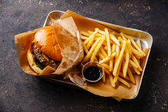 Burger with meat and French fries. In aluminum tray on dark background Stock Photography