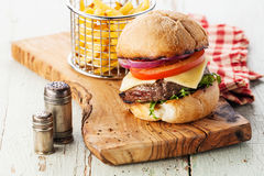 Burger with meat and French fries in basket Royalty Free Stock Images