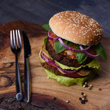Burger with meat on wooden cutting board with fork and knife. Selective focus. Royalty Free Stock Photography