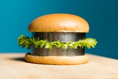 A burger with metal bars instead of cutlets lies on a wooden board. Eating iron, ferrum