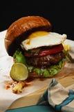Burger mit Ei auf einem hölzernen Brett Stockfotografie