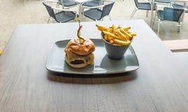 Burger mit französischen gebratenen Kartoffeln lizenzfreie stockbilder