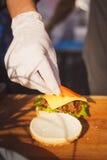 Burger mit Käse und einem Brötchen in der Küche Stockfoto