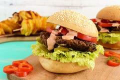 Burger mit Leberkotelett, Tomaten, Essiggurken, Kopfsalat, würziger Soße und einem weichen Brötchen mit Samen des indischen Sesam lizenzfreies stockfoto