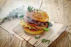 Burger mit Rindfleischkotelett und Frischgemüse ohne schädliche Zusätze für gesunde Nahrung im Rauche lizenzfreie stockbilder