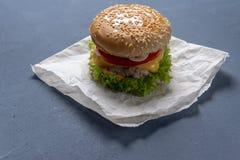 Burger mit Rindfleischpastetchen, Salat, einer Scheibe der Tomate und des Käses, Zwiebeln und Soße mit Paprika in einem gegrillte stockfoto