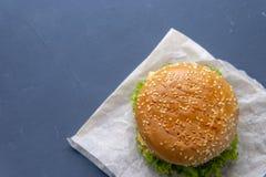 Burger mit Rindfleischpastetchen, Salat, einer Scheibe der Tomate und des Käses, Zwiebeln und Soße mit Paprika in einem gegrillte stockbild
