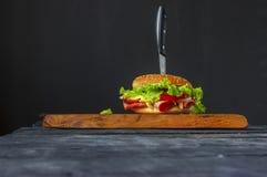 Burger mit Schinken auf einem Schneidebrettmesser durchbohrt Lizenzfreie Stockbilder