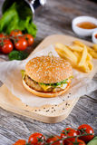 Burger with mushrooms and chop on a wooden stand Stock Image
