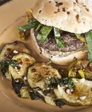 Burger with Onion Bun and Baked Zuchinni. Beef Burger with Onion Bun and Baked Zuchinni royalty free stock images
