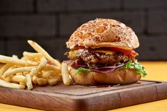 Burger with onion rings, cheese and jack daniel`s sauce. Western style burger with onion rings, cheese and jack daniel`s sauce royalty free stock photo
