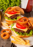 Burger and onion rings. Selective focus on the front burger with onion rings Royalty Free Stock Photos