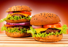 Burger pair. Pair of burgers on wooden board stock photos