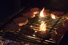 Burger patties on a BBQ grill. Multiple Burger patties cooking on an outdoor BBQ grill with flames Stock Photo