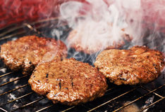 Burger patties on a grill. (selective focus Royalty Free Stock Image