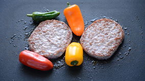 Burger Patty Cooked With Peppers. This is footage of two burger patties getting grilled on a pan with some peppers. Juice meat for a tasty home made fast food stock video footage