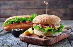 Burger with pickled salmon, lettuce, white onion and capers Royalty Free Stock Image