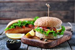 Burger with pickled salmon, lettuce, white onion and capers Royalty Free Stock Photos
