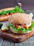 Burger with pickled salmon, lettuce, white onion and capers Royalty Free Stock Images